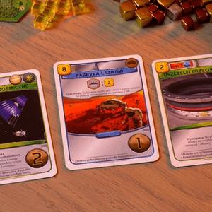 """Karty """"Górnictwo kosmiczne"""", """"Fabryka łazików"""" i """"Uszczelki przeciwpyłowe"""". Zielone karty to karty natychmiastowe, które wywołują efekt w momencie zagrania. Karta niebieska to karta """"aktywna"""", czyli taka, która daje trwały efekt lub akcje, z których gracz może korzystać w trakcie gry. (Terraformacja Marsa)"""