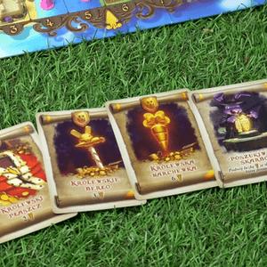 Karty pergaminów leżące na trawie (Królestwo Królików)