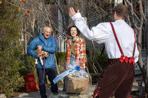 Smiling grandparents receive a gift basket.
