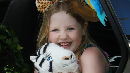 Alyna holding a stuffed tiger smiling