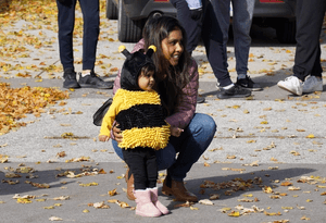 Child in a bumblebee costume with her mother