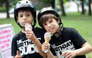 Two kids wearing skateboard helmets eating ice cream.