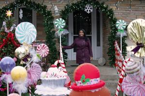 Reneisha on her porch, smiling. Holiday lawn ornaments decorate the foregound.