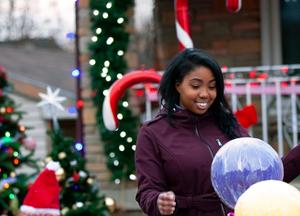 Reneisha smiling after seeing a bunch of balloons.