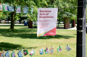 Random Acts of Happiness poster with Koodo masks on a clothesline