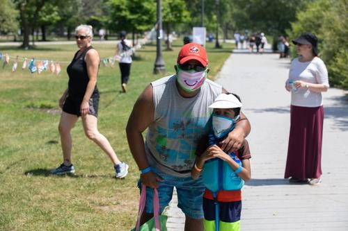 Man and his child wearing happy masks
