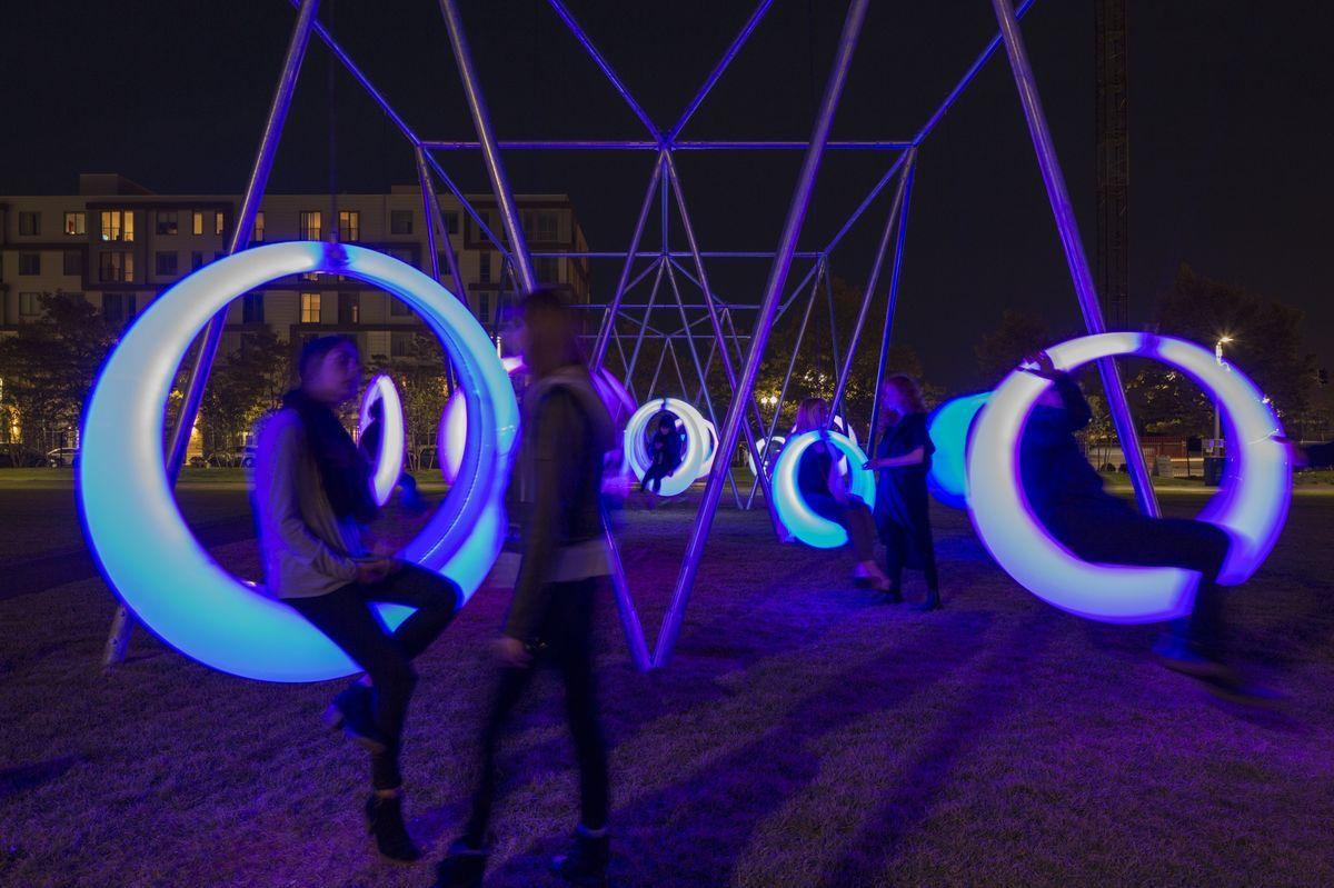 A night time photograph of a swing installation. The swings are internally illuminated and are round rings that people can sit on.