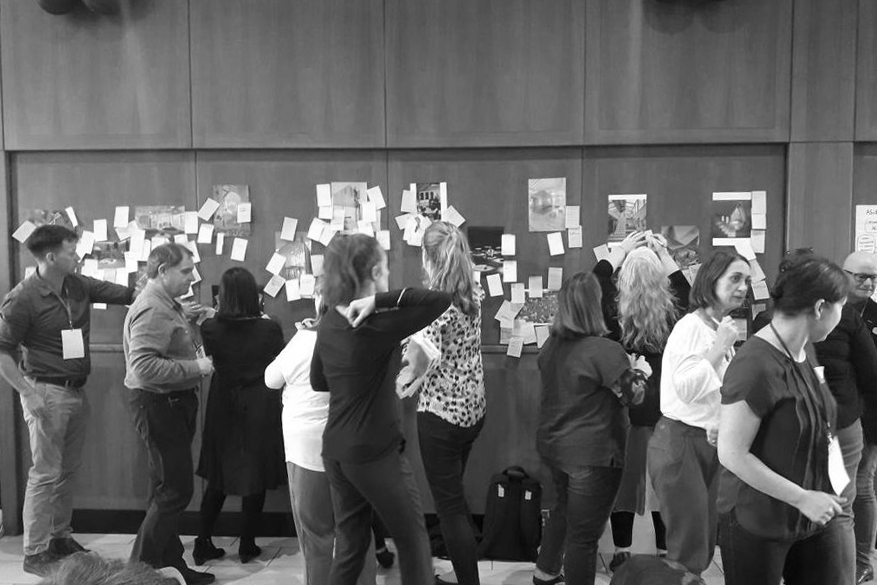 A photograph of a group of people standing and placing yellow sticky notes on images stuck to a wooden paneled wall