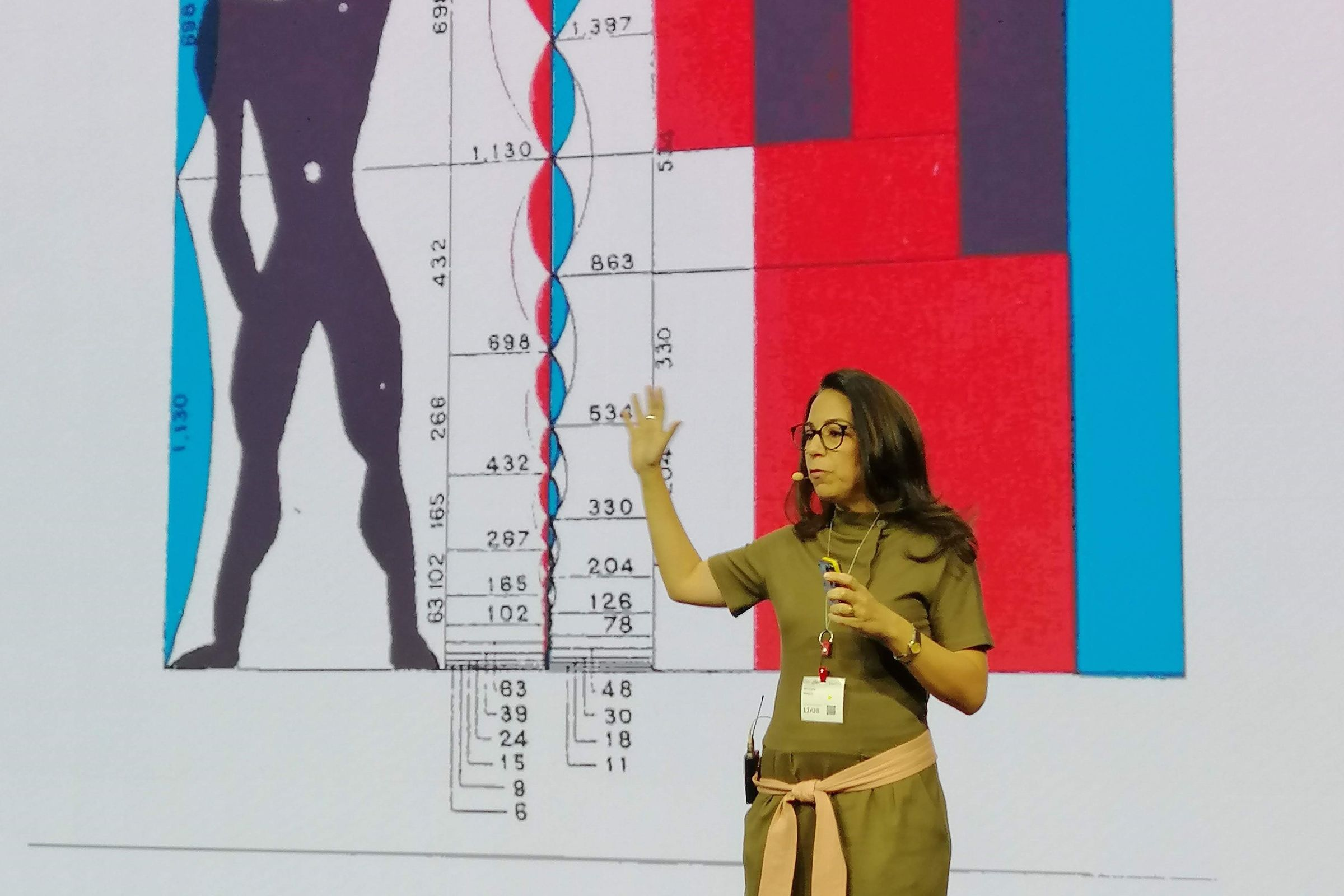 A woman in a yellow top stands on a lit stage in front of a large presentation screen with a red TEDxCairo sign