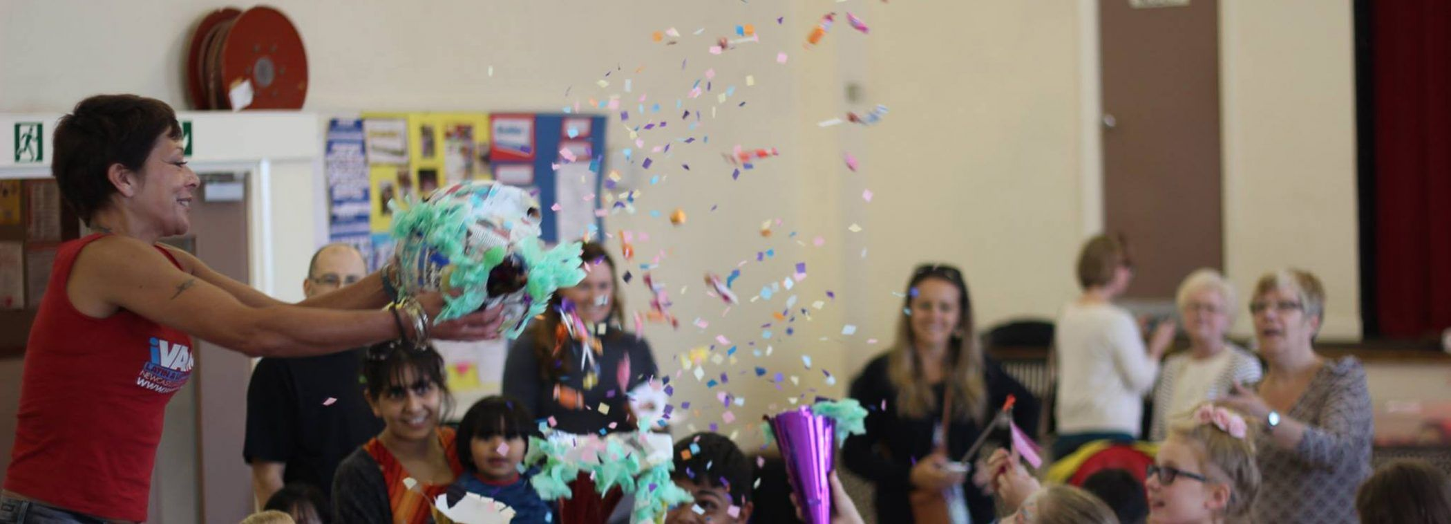 Children playing with a pinata whilst parents and carers look on.