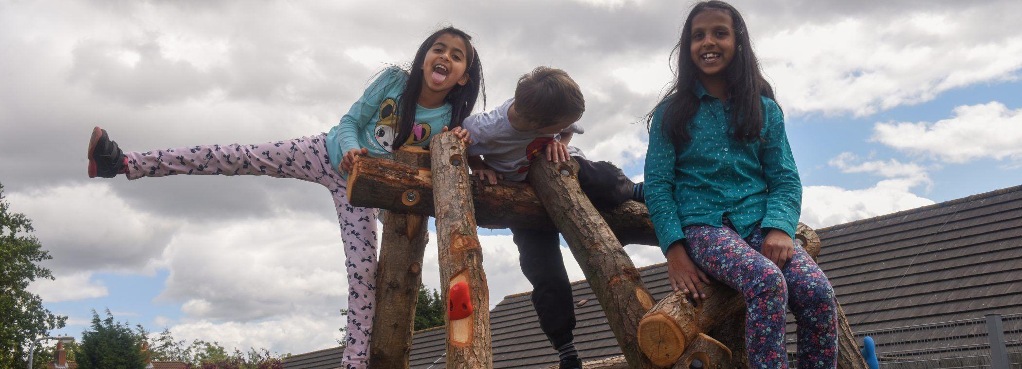 Three children climbing on play equipment outside Far Centre, Fenham.
