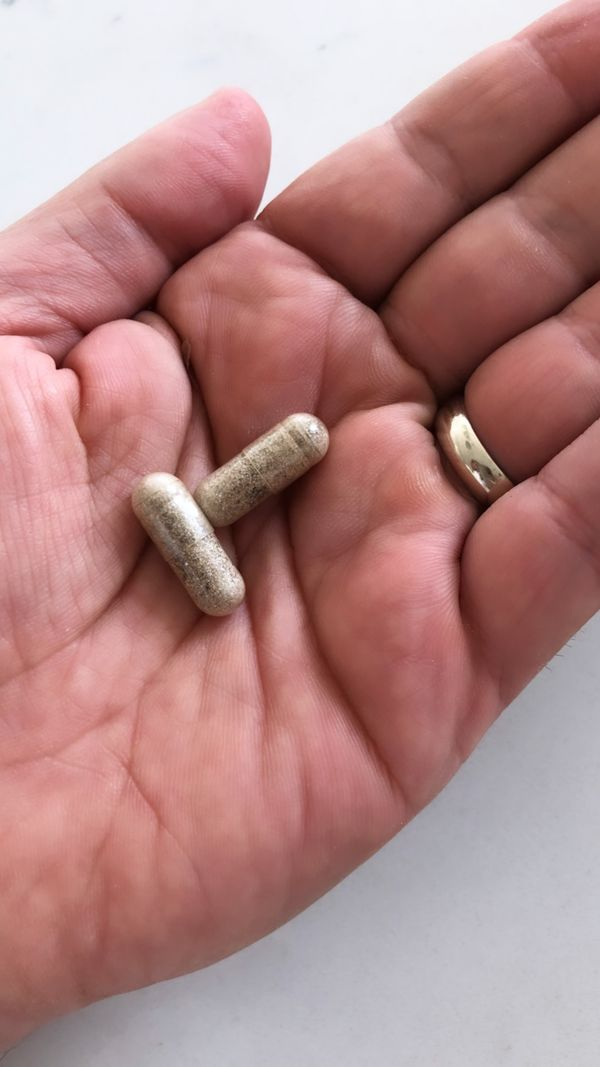 Proper customer holding two sleep supplement capsules in the palm of his hand
