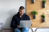 young man in blue sweater on laptop_sleep coach adults_proper
