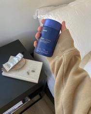 Proper customer holding a bottle of Sleep + Clarity