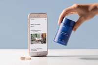 hand holding bottle of sleep supplements next to iphone and capsules_Proper