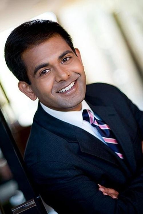 Smiling man wearing a navy suit with a blue and pink striped tie | Ruchir Patel, MD | Member of Proper's Scientific and Medical Advisory Council