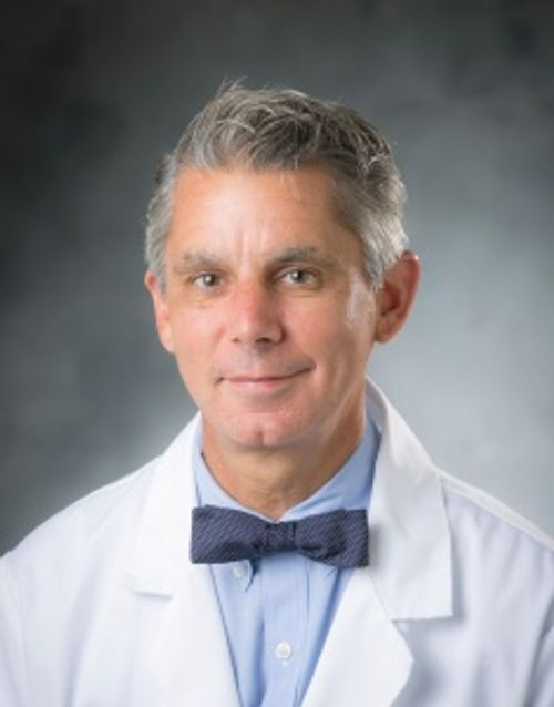 Smiling man wearing a white medical coat and bow tie | David Casarett, MD, MA | Member of Proper's Scientific and Medical Advisory Council