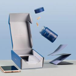 Open blue bottle with capsules flying next to pamphlet and open box