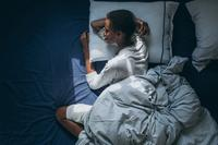 Woman sleeping in a bed with navy sheets | 4 stages of sleep | Proper