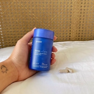Woman holding blue Proper Sleep + Calm bottle, with two capsules on her bed.
