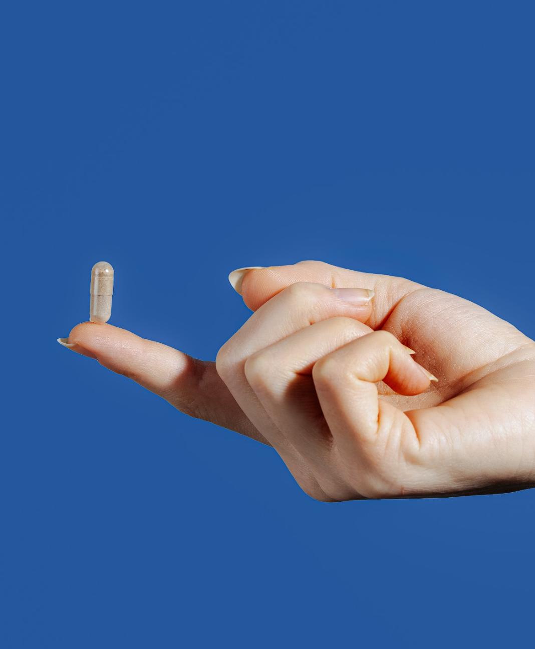 single pill resting on the pointer finger | gaba for sleep | Proper