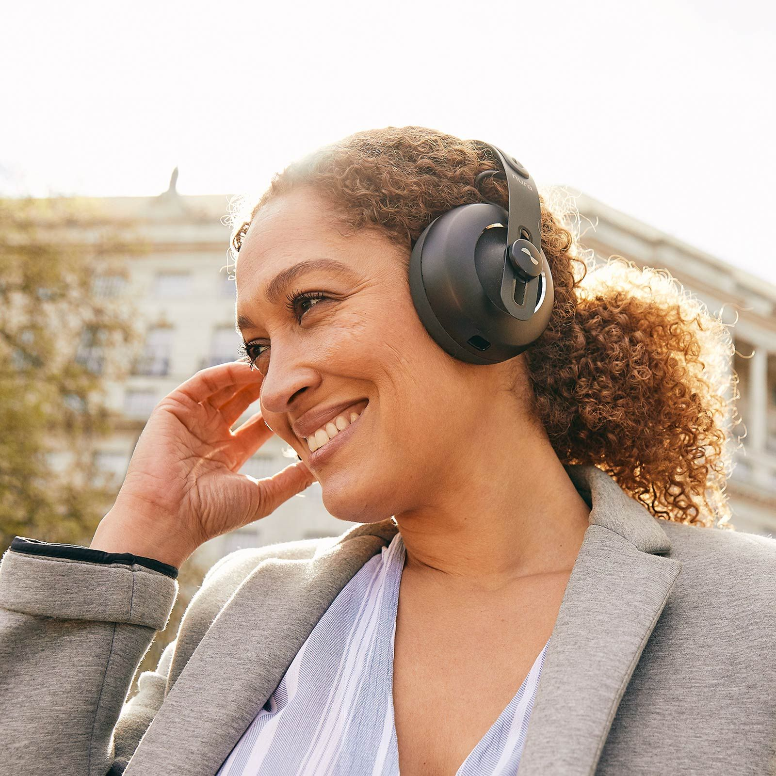 Person outside with NURAPHONE headphones on tapping on a touch button to enable social mode