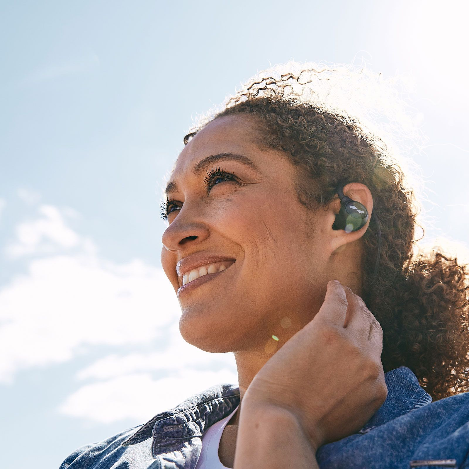 Person outside with NURALOOP earbuds in ears about to tap a touch button to enable a feature