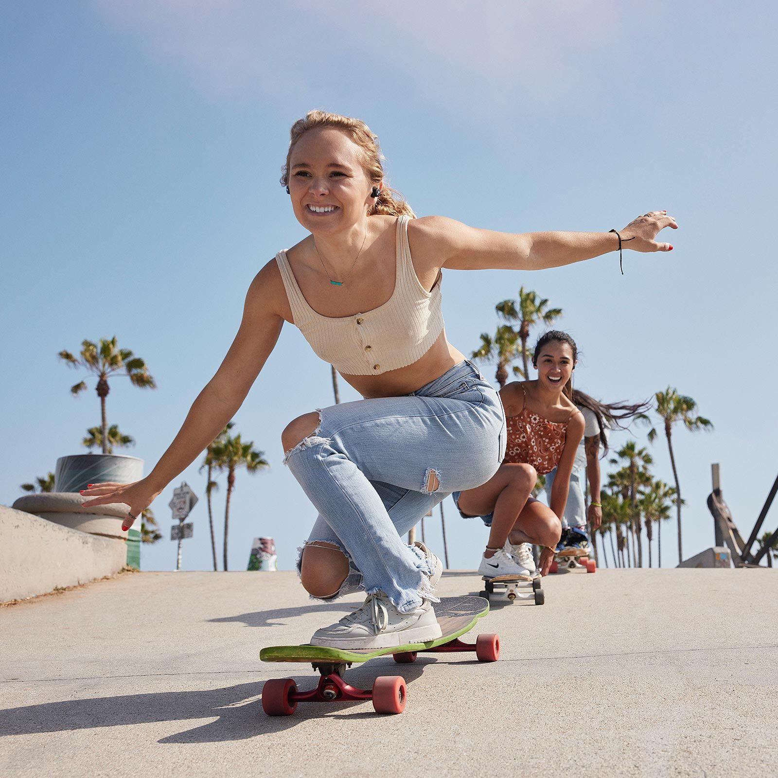 Longboard skater with NURABUDS earbuds in ears skating with friends