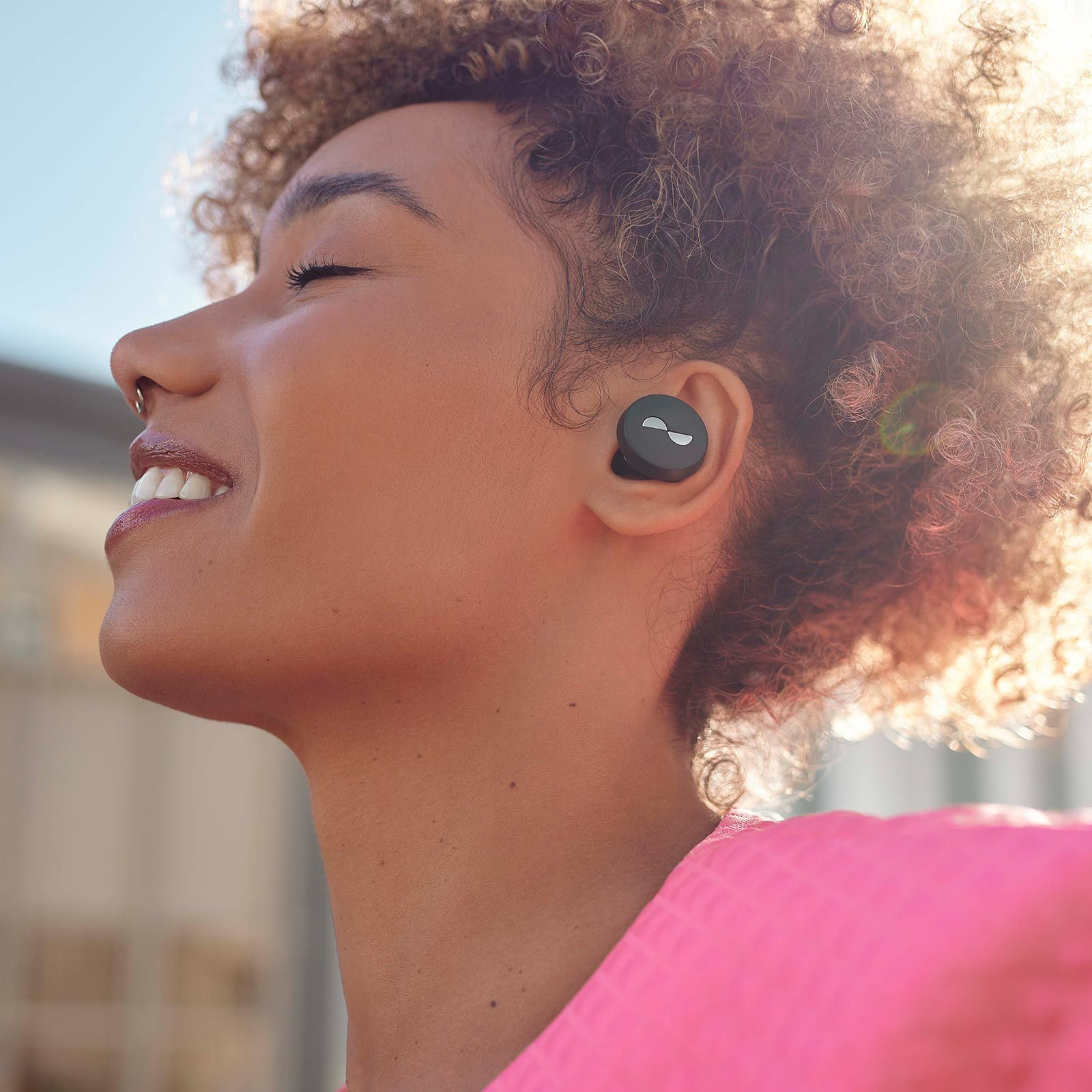 Person with eyes closed listening to sound with NURATRUE earbuds in ears