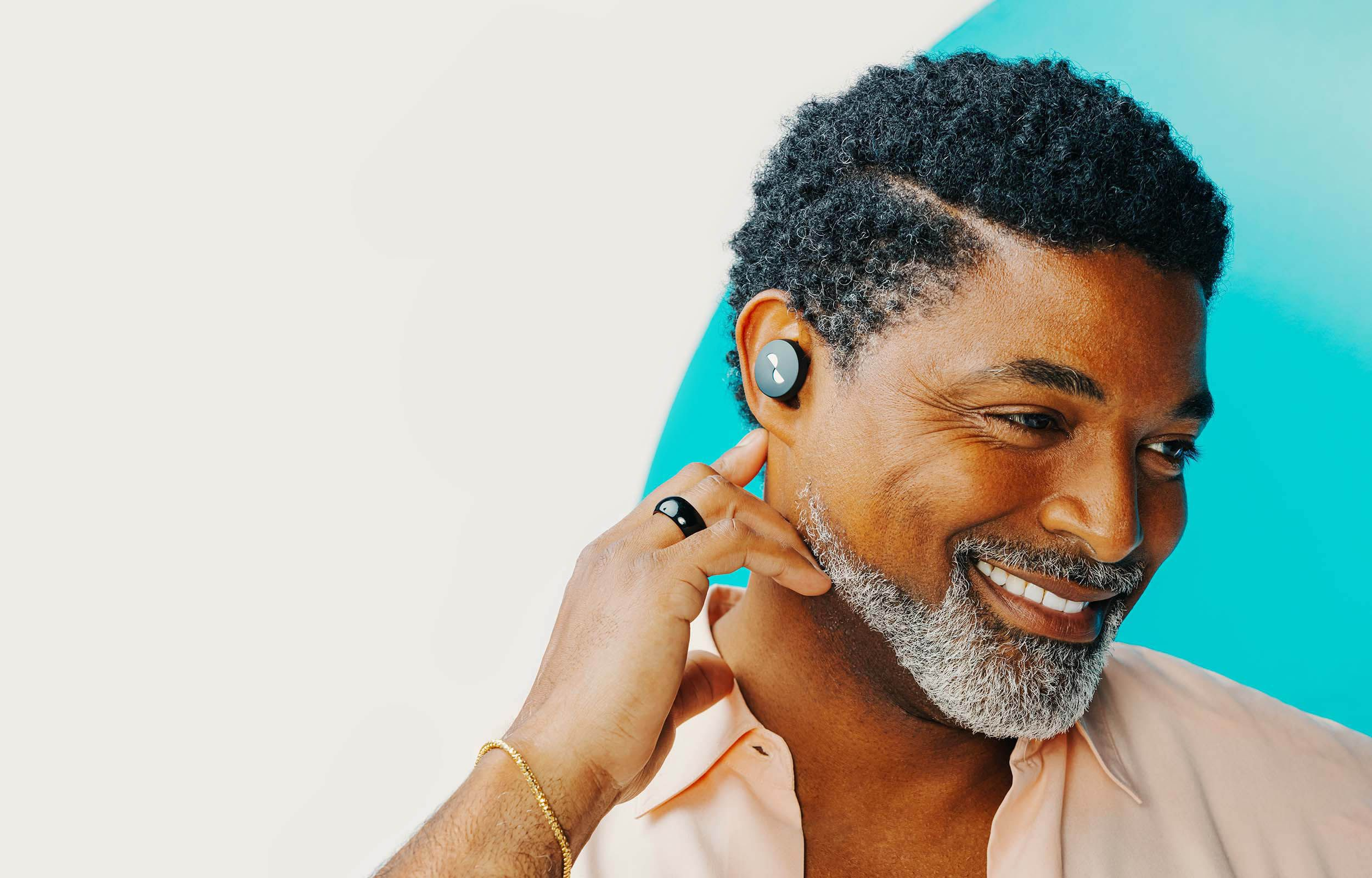 Person posing with NURATRUE earbuds in ears