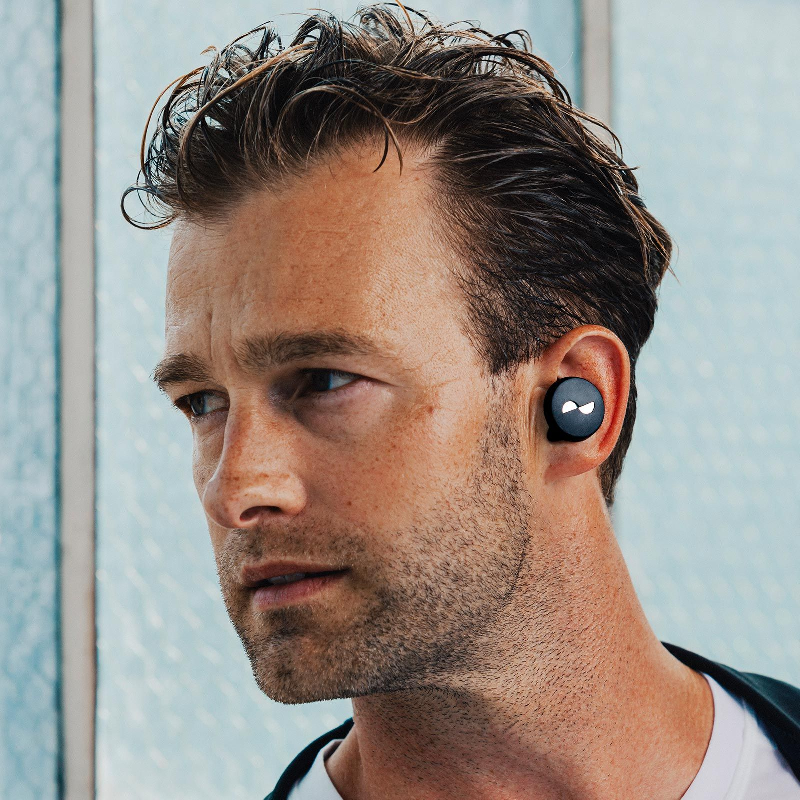 Person covered in sweat with NURATRUE earbuds in ears