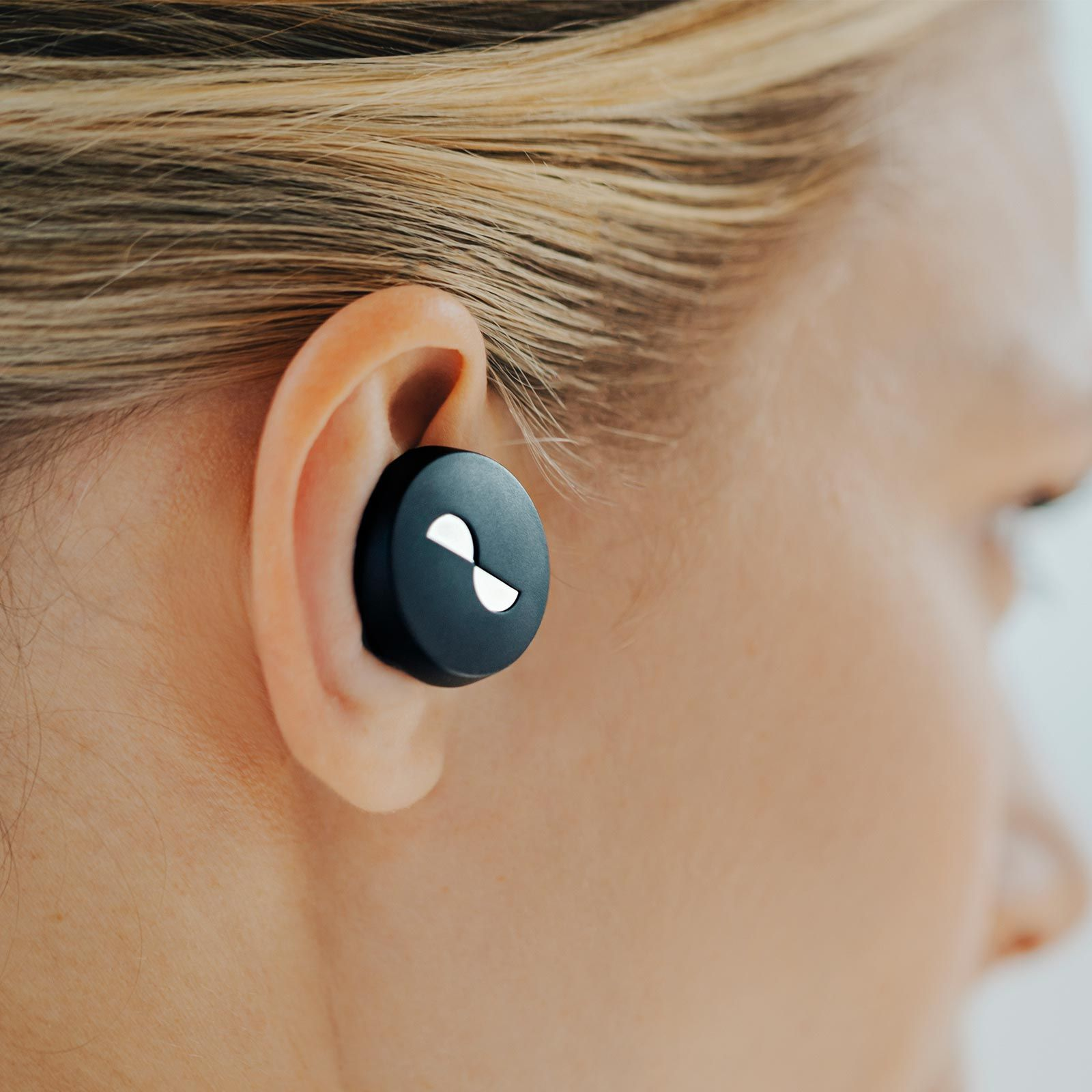 Close-up of NURATRUE earbuds in person's ears
