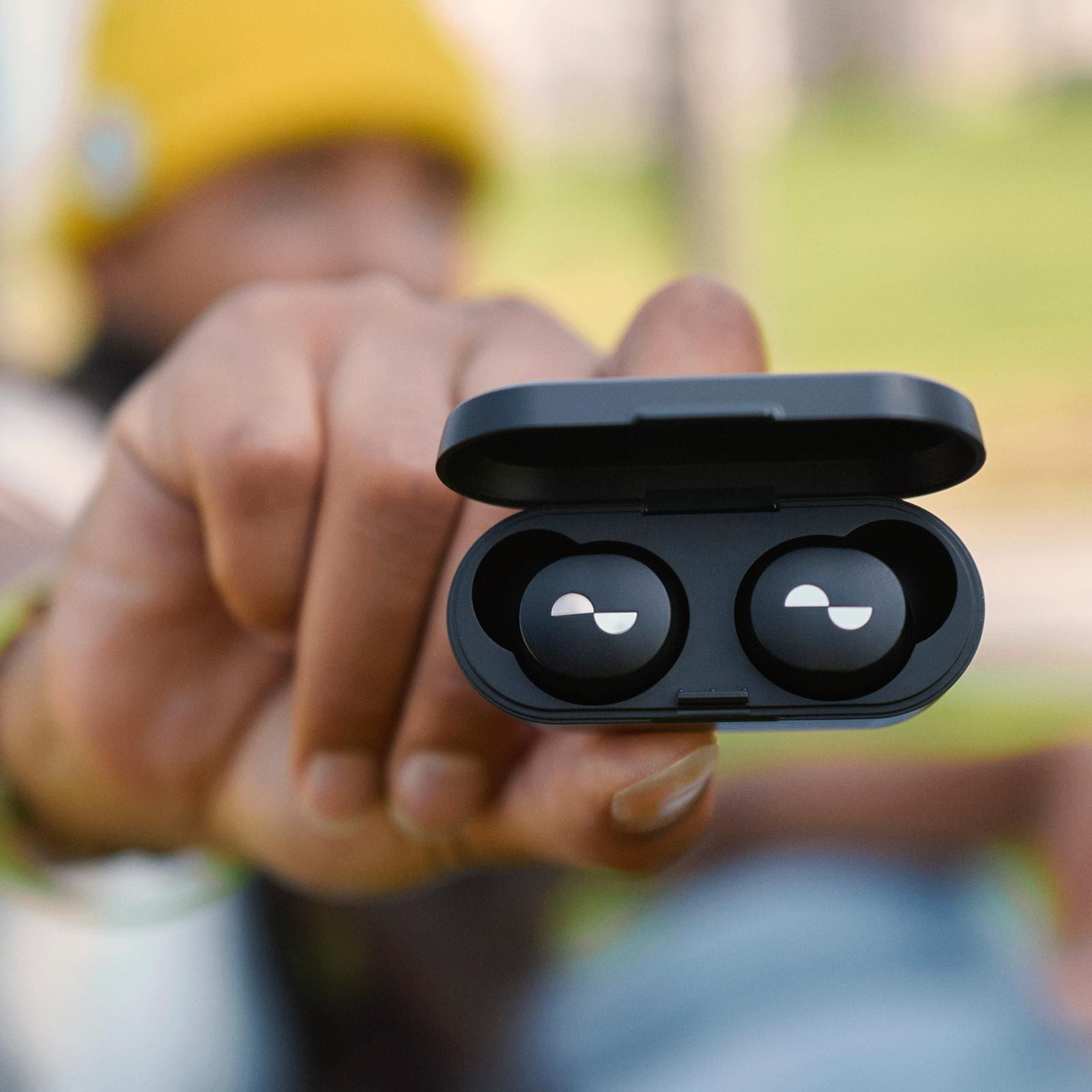 Close-up of NURABUDS earbuds in battery case with person holding them out-of-focus