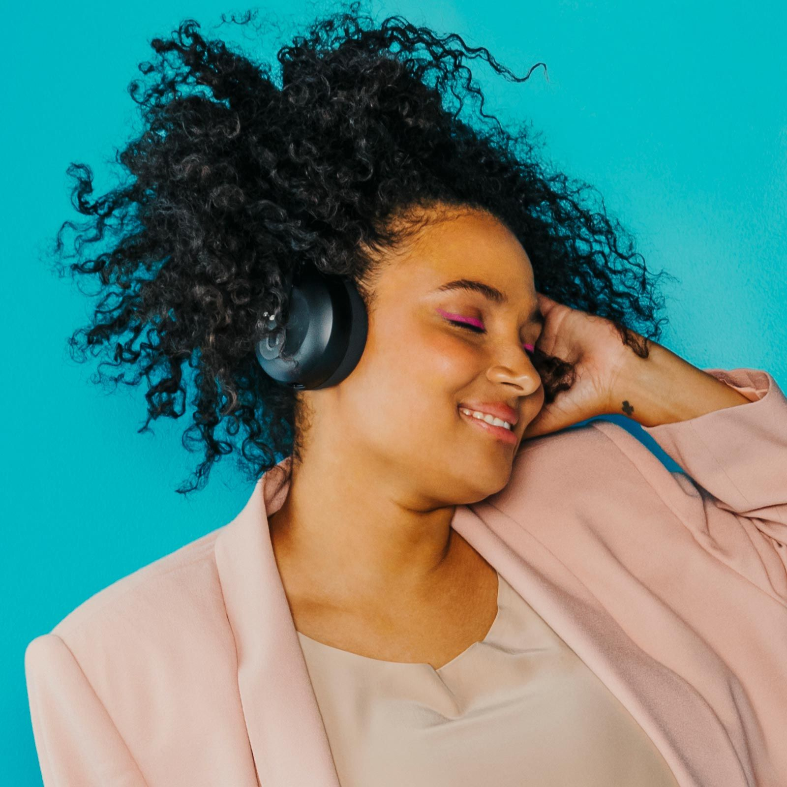 Person with eyes closed with NURAPHONE headphones on listening to sound