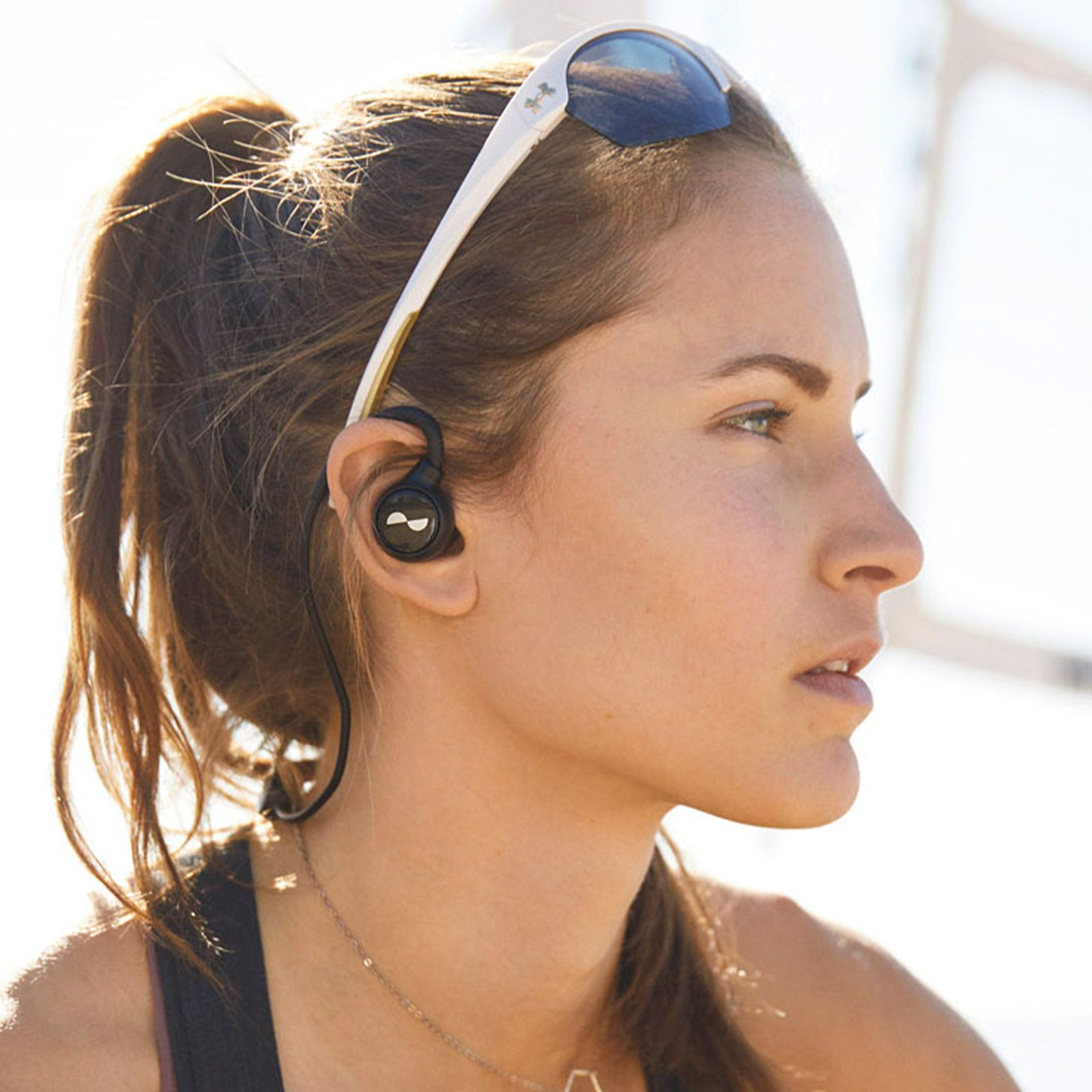 Person wearing sunglasses outside with NURALOOP earbuds in ears