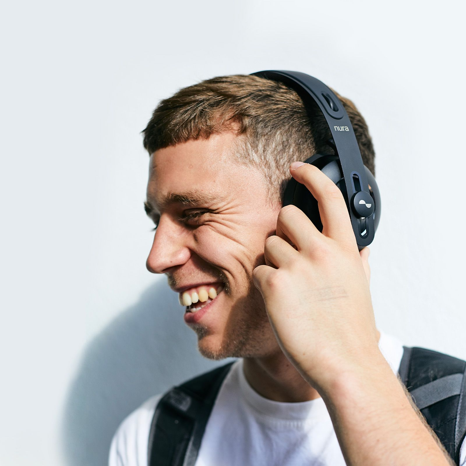 Person laughing with their NURAPHONE headphones on ears whilst enabling active noise cancellation