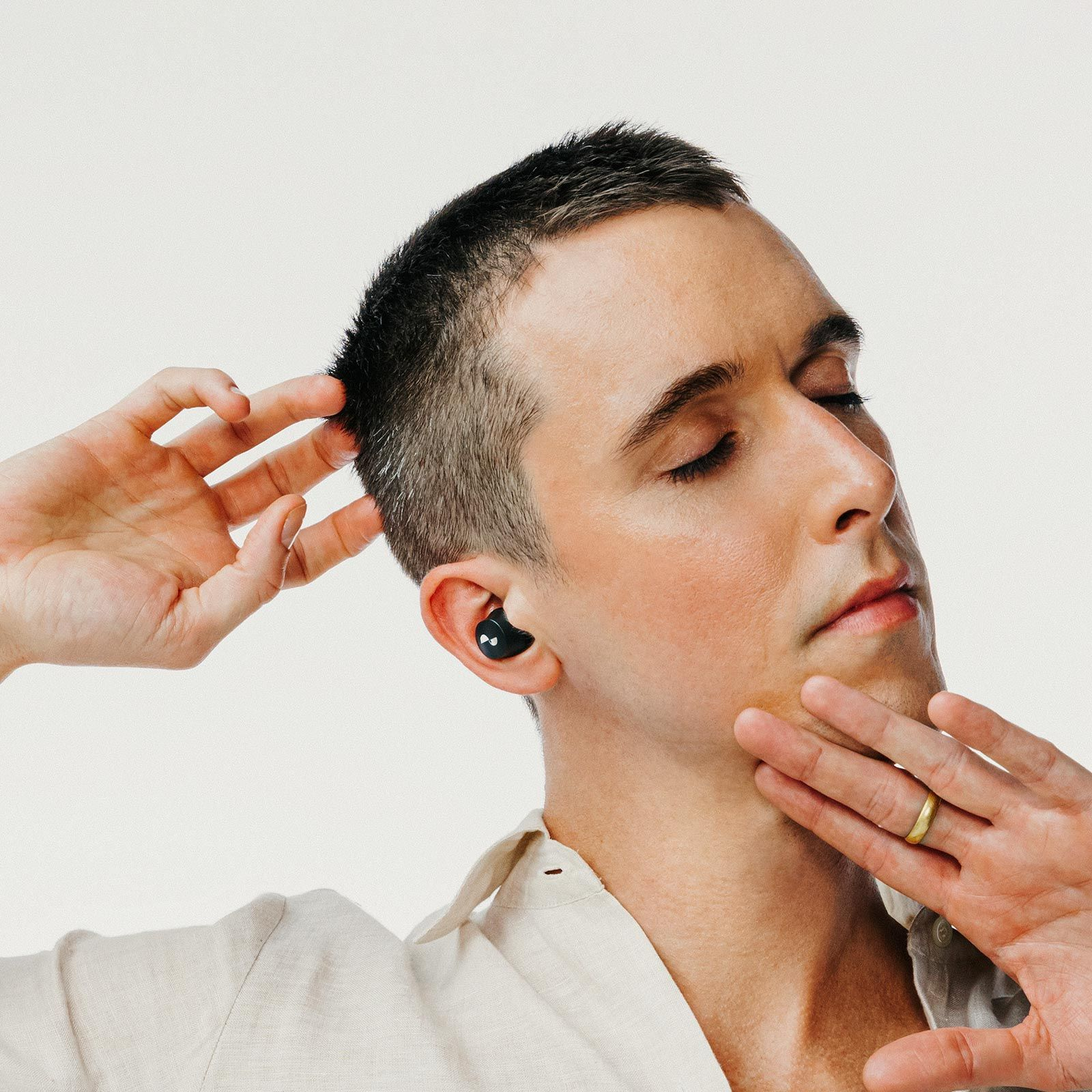 Person with eyes closed with NURABUDS earbuds in ears