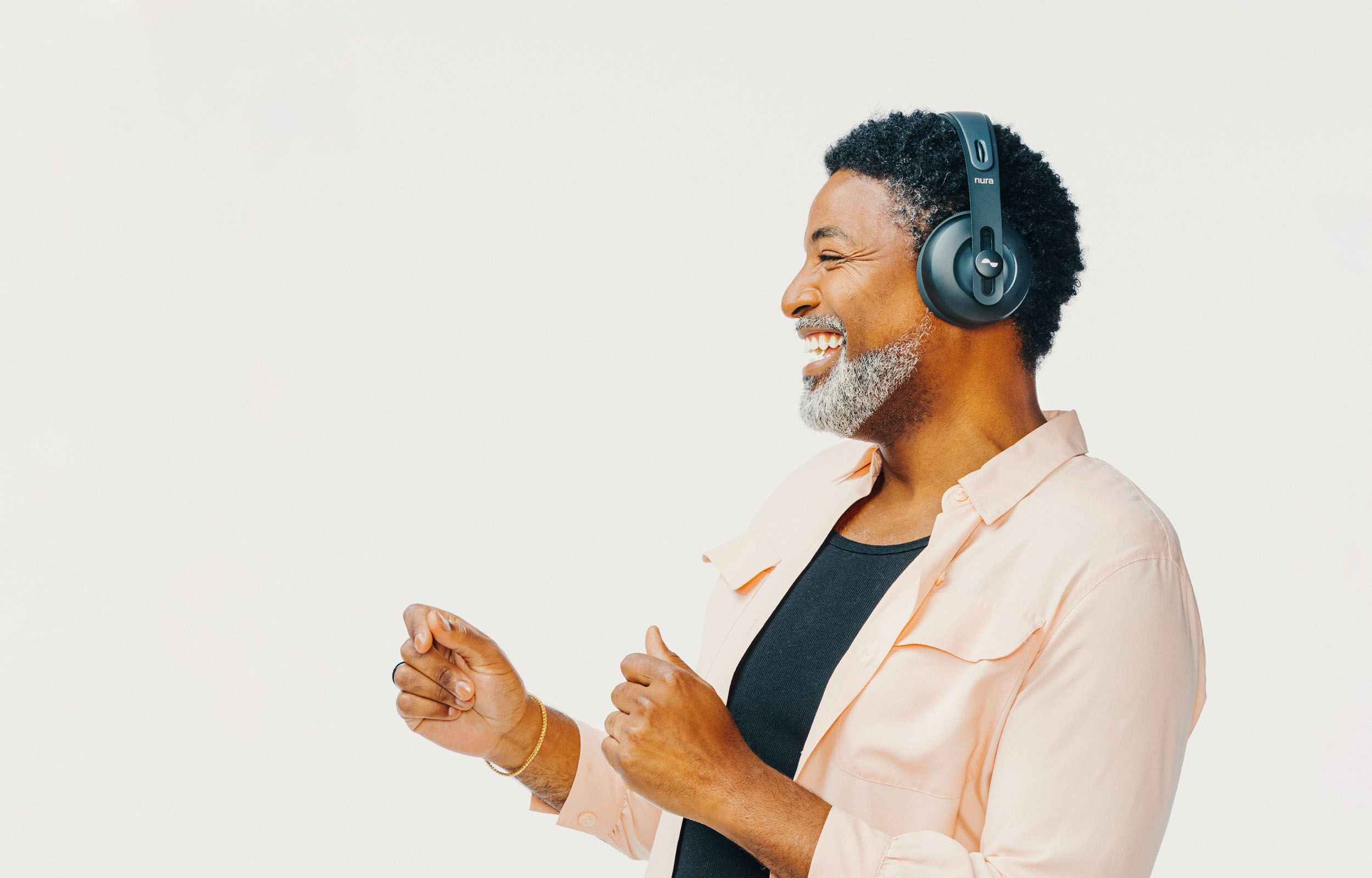 Person laughing and dancing with NURAPHONE headphones on ears