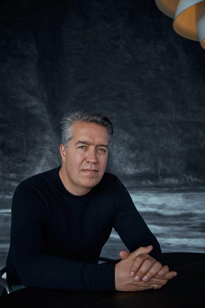 En mann med sort hår sitter og ser mot kamera med hendene foldet på bordet foran seg.