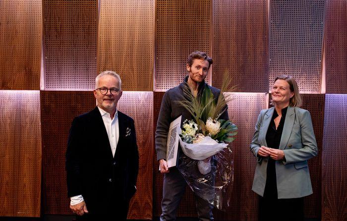 Vinner av Aspelin Ramm-prisen, Hugo, står med diplom og blomster og smiler til kamera. Til hans venstre side står Aspelin Ramm-sjef, Gunnar Bøyum og til høyre står juryleder Marianne Skjulhaug fra AHO. Begge smiler.