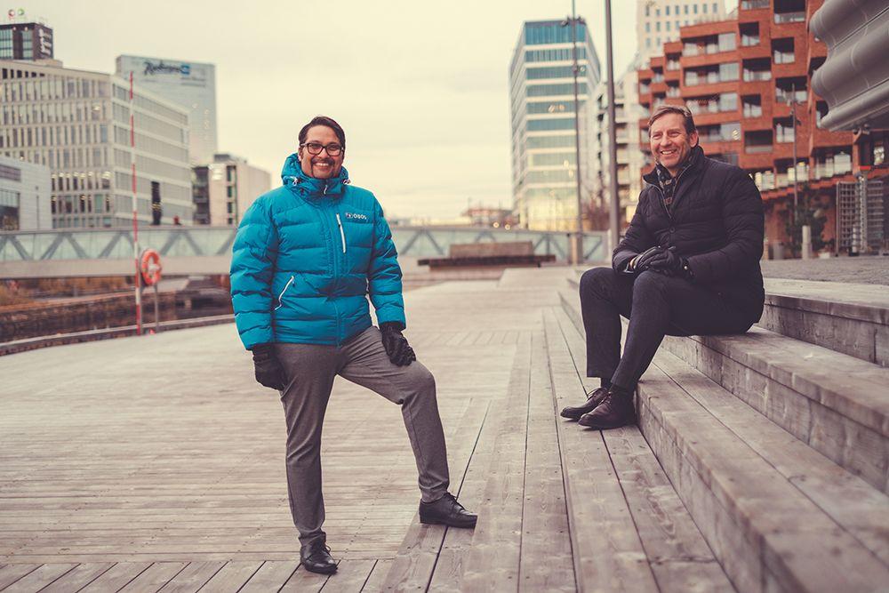 OBOS-sjef, Daniel K. Siraj og styreleder i OMA, Mathis Grimstad smiler på Munch Brygge i Bjørvika
