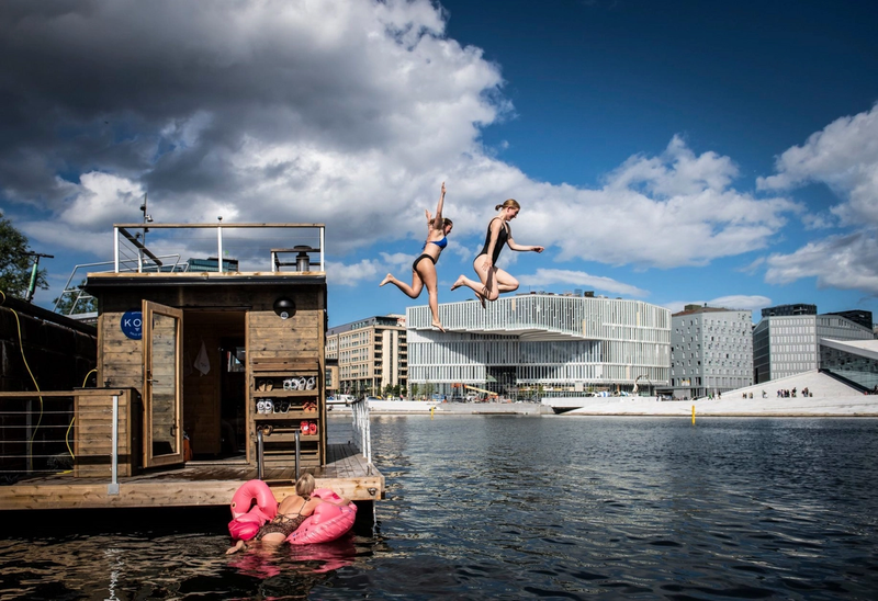 Tre jenter som hopper i sjøen og bader i Bjørvika med utsikt til Operaen og Deichman