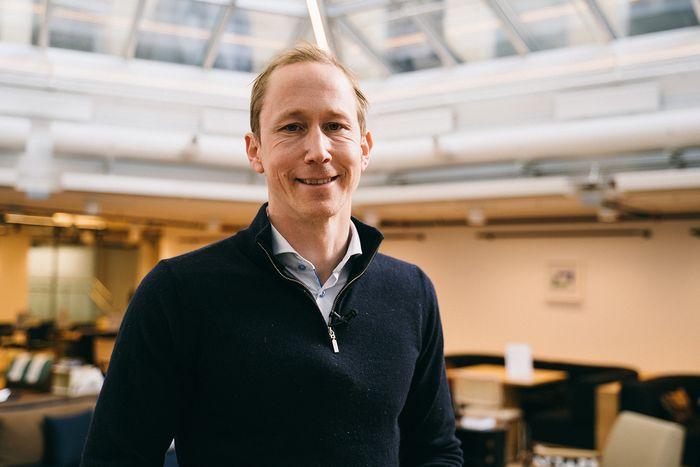 Henrik Botten Taubøll snakker om framtidens kontormarked. Han står i et kontorlandskap og smiler til kamera med mikrofonmygg på genseren.