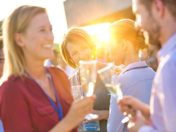 Kvinne og mann som skåler med champagne. Flere folk i bakgrunnen. Feststemning,