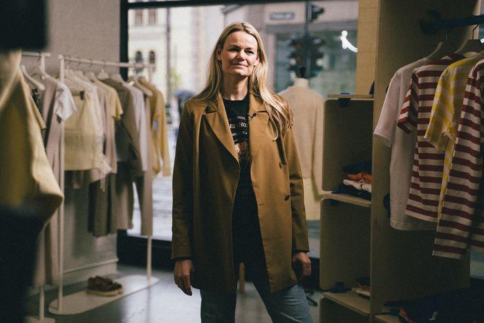 Susanne Holzweiler snakker om retailtrender etter pandemien. Hun har lyst langt hår og står inne i en klesbutikk med opphengte klær rundt seg.