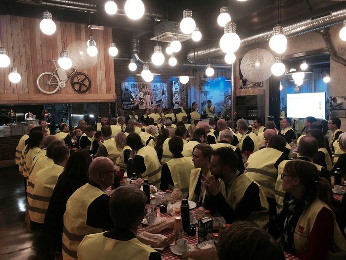 Folk samlet rundt flere frokostbord. Alle har på gule Veidekke-vester.