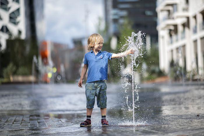 En lyshåret gutt på ca. 5 år leker med vann fra en fontene.