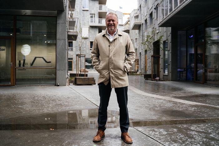 Byrådsleder Raymond Johansen står mellom boligbygg og smiler til kamera.