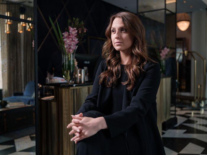 Emilie Stordalen sitter på en stol med beina i kors ved en hotellresepsjon. Hun er kledd i sort dress.