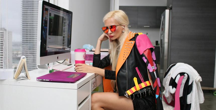 Fancy dame i fargerike klær sitte ved en pult med datamaskin